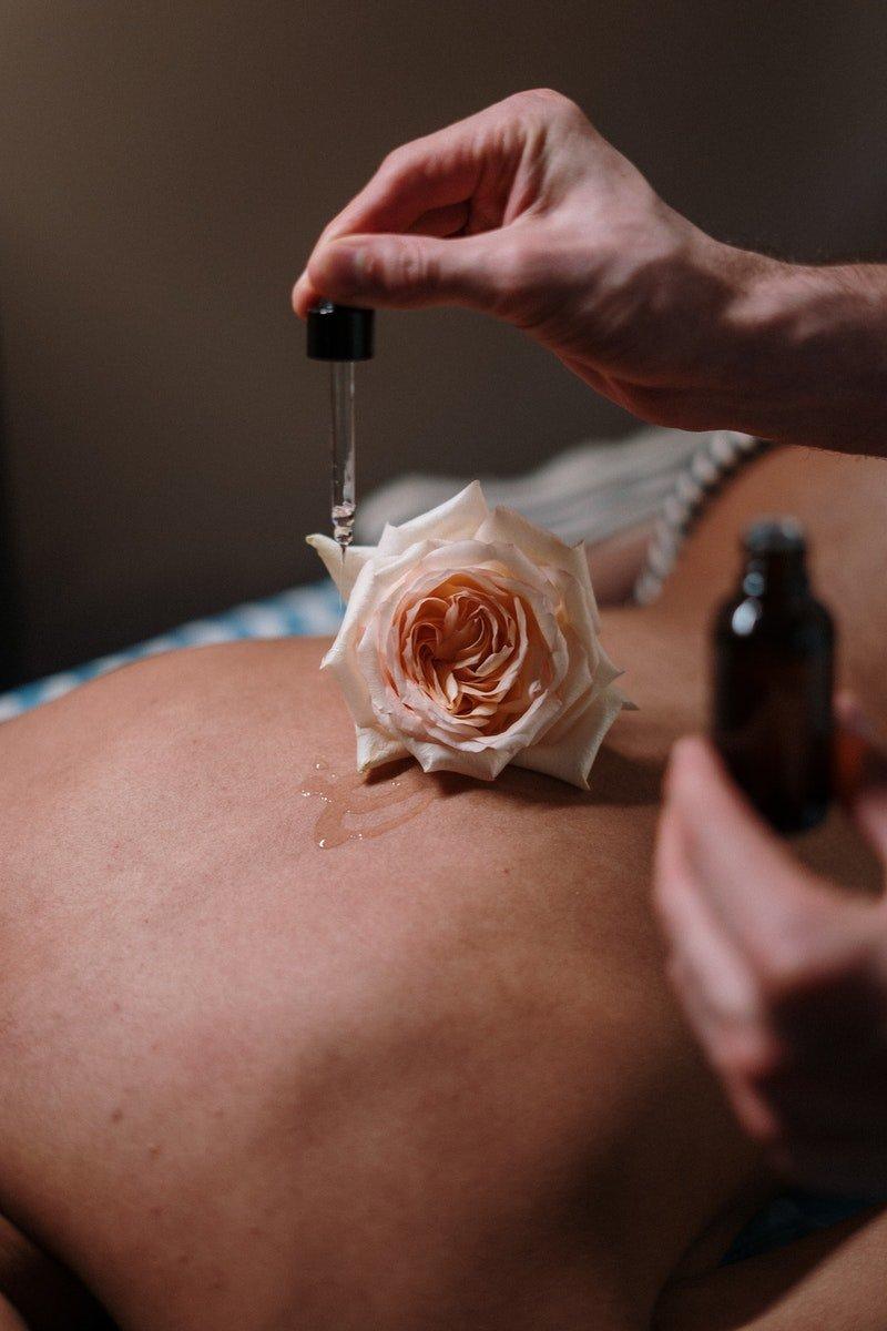Rose und Öl auf einem nackten Rücken während einer Massage